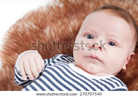 Closeup portrait of adorable baby lying on fur - stock photo