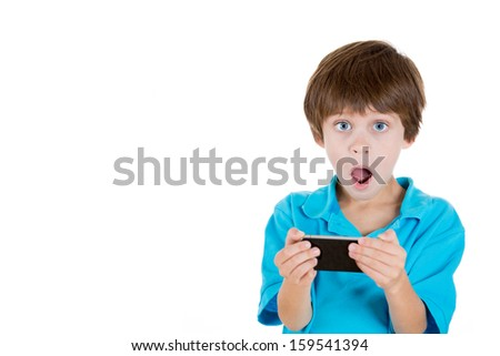 Closeup portrait of adorable boy holding cell phone in hands and shocked by what he sees isolated on white background with copy space