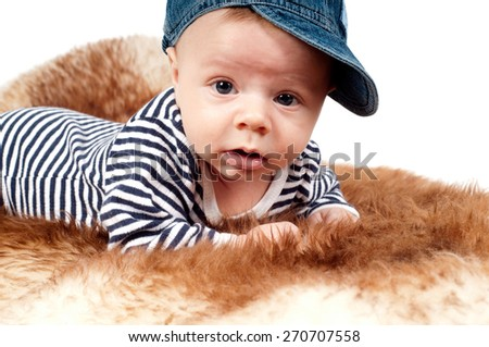 Closeup portrait of adorable child in hat lying on fur - stock photo