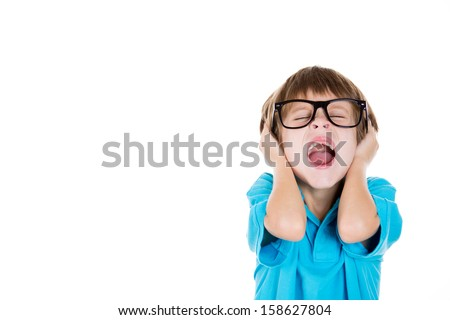 Closeup portrait of adorable kid with black glasses covering ears as if something is loud or he doesn't want to hear something, isolated on white background with copy space - stock photo