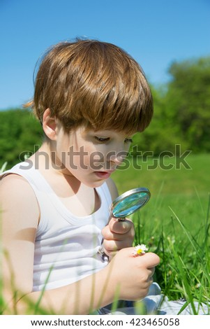 Closeup Portrait Of Adorable Little Boy Watching Daisy Carefully Through The Magnifying Glass On Green Meadow On Sunny Spring Day   - stock photo