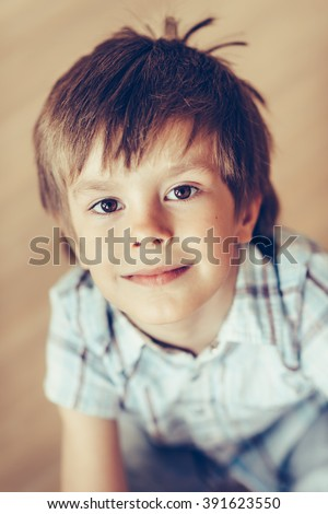 Closeup portrait of adorable smiling little boy with brown eyes wearing checkered shirt sitting on floor looking at camera. Happy childhood concept, selective focus on eyes, top view, instagram filter - stock photo