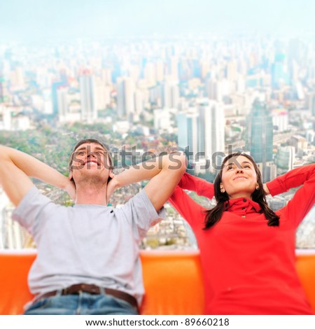 Closeup portrait of adult couple sitting on their sofa against big city panoramic view and dreaming about something. Planning future concept