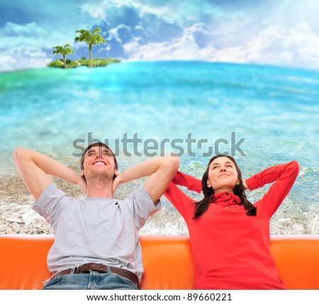 Closeup portrait of adult couple sitting on their sofa at sunny beach against ocean with island and dreaming about something. Planning future vacation concept