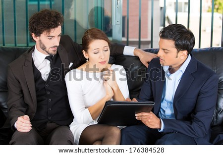 Closeup portrait of agent giving bad news to rich unhappy couple man woman sitting on black couch in house, apartment isolated on city urban background. Financial budget troubles, adverse life events - stock photo