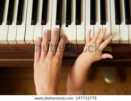 Closeup portrait of an adult hand playing piano with baby hand - stock photo