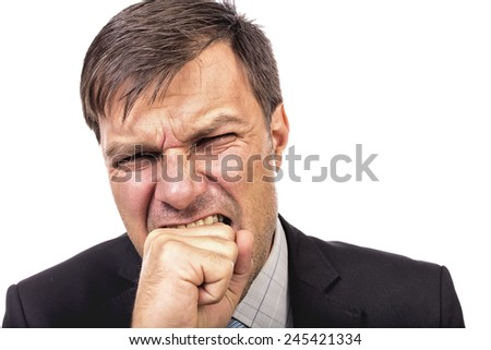 Closeup portrait of an angry guy biting his fist against white background - stock photo