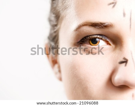 Closeup portrait of an attractive Caucasian lady whose face is marked with lines for facial cosmetic surgery - stock photo