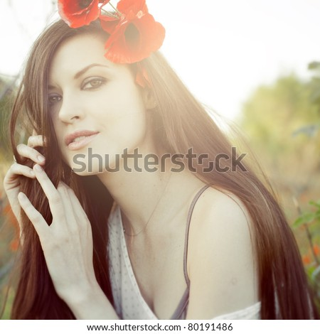 Closeup portrait of an attractive girl in a poppy field at sunset (square) - stock photo