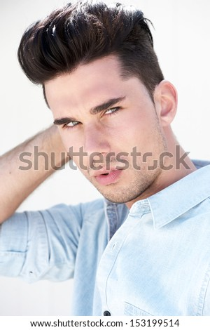Closeup portrait of an attractive male fashion model with hand in hair