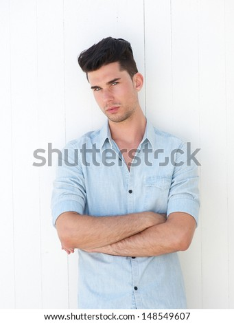 Closeup portrait of an attractive male with arms crossed on white background