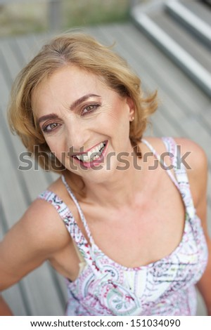 Closeup portrait of an attractive older female smiling outdoors - stock photo
