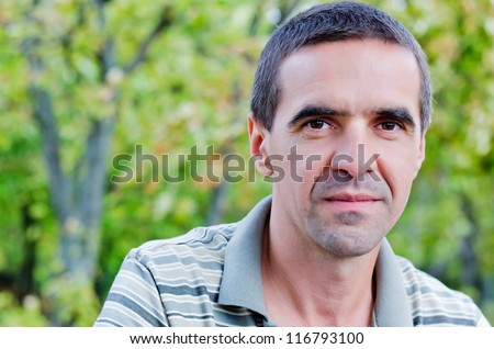 Closeup portrait of an attractive serious middle-aged man looking directly into the camera standing outdoors amongst trees with copyspace - stock photo