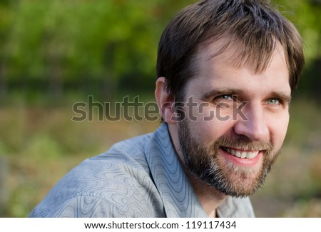 Closeup portrait of an attractive serious middle-aged man standing outdoors amongst trees with copyspace - stock photo