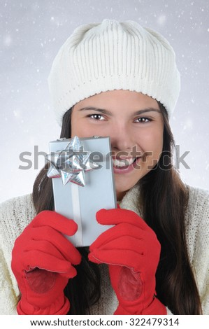 Closeup portrait of an attractive teenage girl wearing a knit cap holding a small Christmas present in front of her. Vertical format with a snowy background. - stock photo