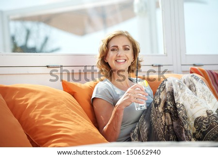 Closeup portrait of an attractive woman holding drinking glass and relaxing outdoors - stock photo