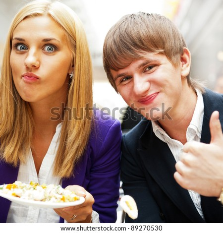 Closeup portrait of an attractive young couple eating fruit salad at college dining room - stock photo