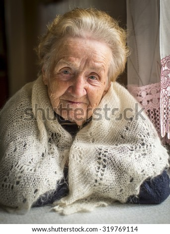 Closeup portrait of an elderly woman sitting at the table. - stock photo