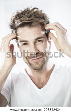 closeup portrait of an handsome man examining his hairs - stock photo