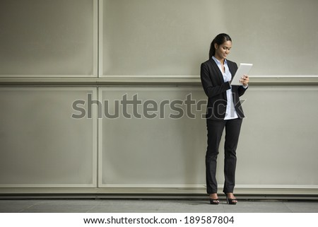Closeup Portrait of an Indian businesswoman standing outside using a Tablet touchpad - stock photo