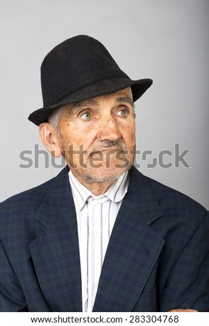 Closeup portrait of an old man with hat over gray background - stock photo