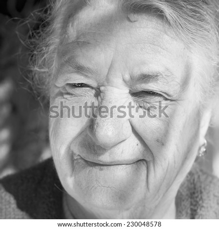 Closeup portrait of an old woman. She has a smile on her face even though she's not nice. - stock photo