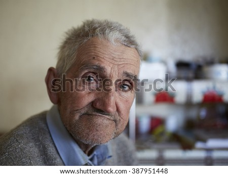 Closeup portrait of an 80 years old farmer indoor - stock photo