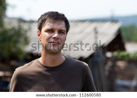 Closeup portrait of an young man outside, at countryside, in a sunny day - stock photo
