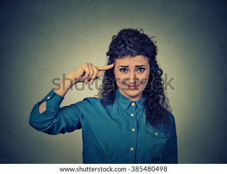 Closeup portrait of angry annoyed young woman gesturing with her finger against temple asking are you crazy? Isolated on gray wall background. Negative emotions facial expression feeling body language - stock photo
