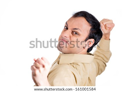 Closeup portrait of angry, mad, furious man, worker, employee, businessman in brown shirt raising fists about to hit you, at camera gesture, isolated on white background. Negative human emotions - stock photo