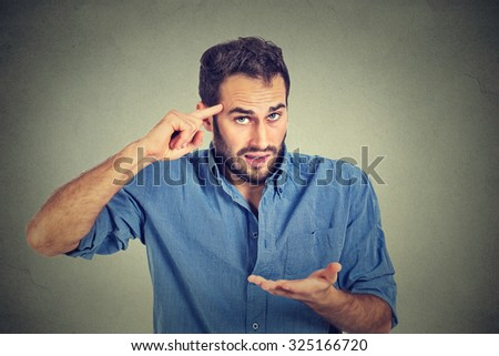 Closeup portrait of angry mad young man gesturing with his finger against temple asking are you crazy? Isolated on gray wall background. Negative emotions facial expression feeling body language - stock photo