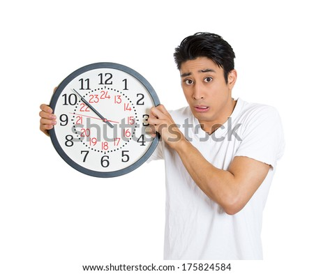 Closeup portrait of anxious business man, funny student, leader holding clock very stressed running out, pressured by lack of time trying to stop hold it late for meeting, isolated on white background