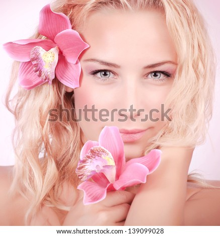 Closeup portrait of attractive blond female with gentle pink orchid flower in hair, skin care, perfect natural makeup, beauty salon - stock photo