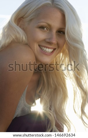Closeup portrait of attractive blond woman smiling on a sunny day - stock photo