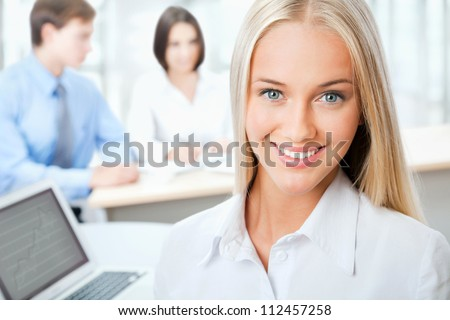Closeup portrait of attractive business woman smiling with colleagues working in background - stock photo