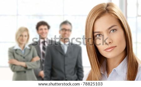 Closeup portrait of attractive businesswoman in focus, with team in background.? - stock photo