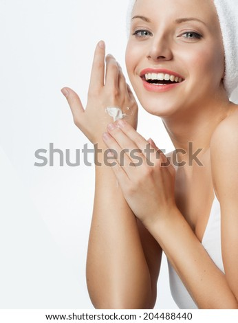 closeup portrait of attractive  caucasian smiling woman blond isolated on white studio shot lips toothy smile face applying cream head and shoulders looking at camera blue eyes tooth - stock photo