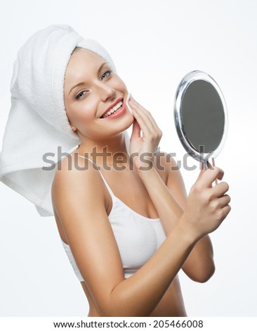 closeup portrait of attractive  caucasian smiling woman blond isolated on white studio shot lips toothy smile face hair head and shoulders looking at camera blue eyes towel mirrow cleaning cotton disc - stock photo