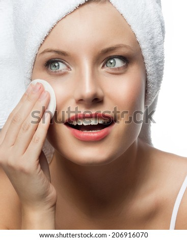 closeup portrait of attractive  caucasian smiling woman blond isolated on white studio shot lips toothy smile face head and shoulders l blue eyes cleaning face cotton disc - stock photo