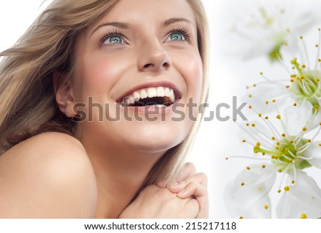 closeup portrait of attractive  caucasian smiling woman blond isolated on white studio shot lips toothy smile face hair head and shoulders looking up blue eyes tooth spring flowers aroma - stock photo