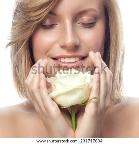 closeup portrait of attractive  caucasian smiling woman blond isolated on white studio shot lips toothy smile face hair head and shoulders  eyes closed hands white rose flower aroma - stock photo
