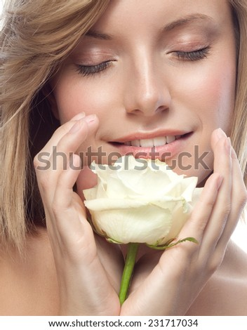 closeup portrait of attractive  caucasian smiling woman blond isolated on white studio shot lips face hair head and shoulders eyes closed flower white rose aroma - stock photo