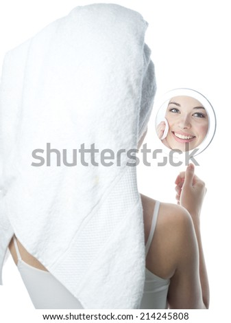 closeup portrait of attractive  caucasian smiling woman brunette isolated on white studio shot lips toothy smile face  head and shoulders looking at mirrow cleaning face cotton disc - stock photo