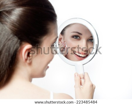 closeup portrait of attractive  caucasian smiling woman brunette isolated on white studio shot lips toothy smile face hair head and shoulders looking at  mirror cleaning face cotton disc - stock photo