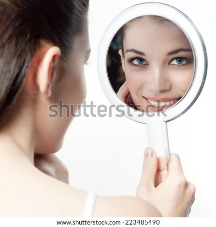 closeup portrait of attractive  caucasian smiling woman brunette isolated on white studio shot lips toothy smile face hair head and shoulders looking at  mirror cleaning face  - stock photo