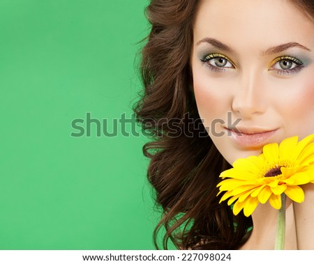 closeup portrait of attractive  caucasian smiling woman brunette isolated on white studio shot lips  face hair head and shoulders looking at camera makeup yellow flower spring summer - stock photo