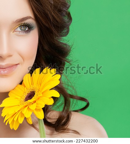 closeup portrait of attractive  caucasian smiling woman brunette isolated on white studio shot lips  face hair head and shoulders skin yellow flower makeup - stock photo