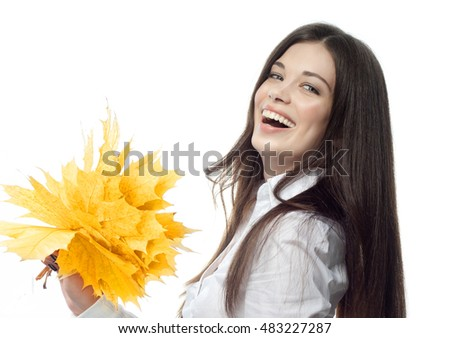 closeup portrait of attractive  caucasian smiling woman brunette isolated on white studio shot lips toothy smile face hair head and shoulders looking at camera hand holding yellow marple autumn leaves
