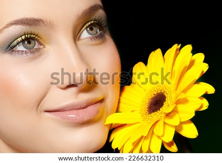 closeup portrait of attractive  caucasian smiling woman brunette studio shot lips toothy smile face  head eyes makeup flower yellow skin - stock photo