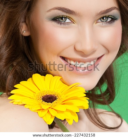 closeup portrait of attractive  caucasian smiling woman brunette studio shot lips toothy smile face hair head and shoulders looking at camera tooth skin makeup yellow flower - stock photo
